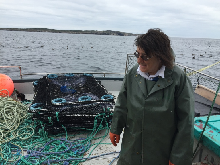 Marie Payne on deck with a colllapsed cod pot in the back ground.