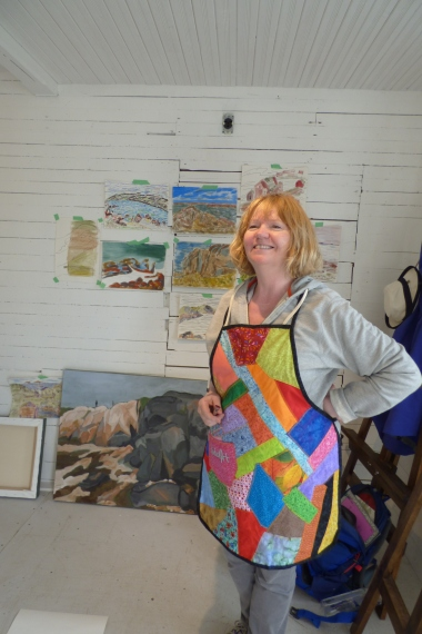 Sherry posed in front of her work on the wall and Janice Thomson's painting on the floor.